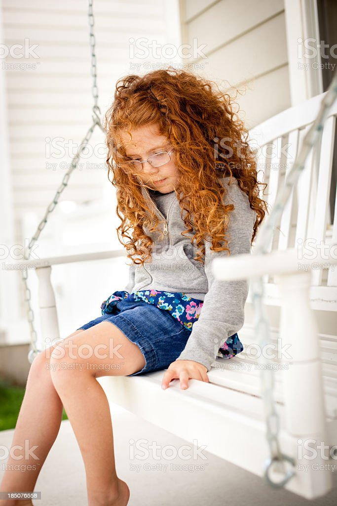 Serious/Sad Little Girl Sitting Alone On Porch Swing royalty-free stock photo