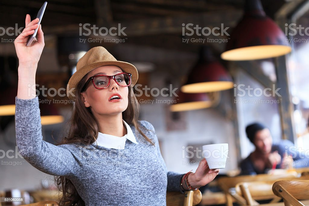 Seriuos young woman calling the waiter stock photo
