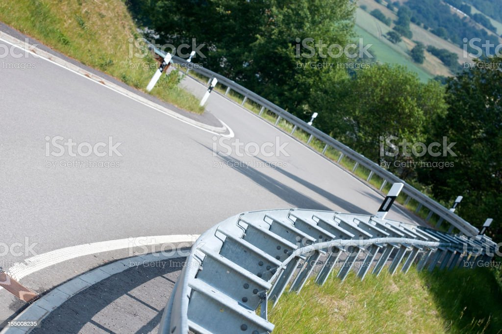 Serpentine country road, asphalt curve - focus on guardrail royalty-free stock photo