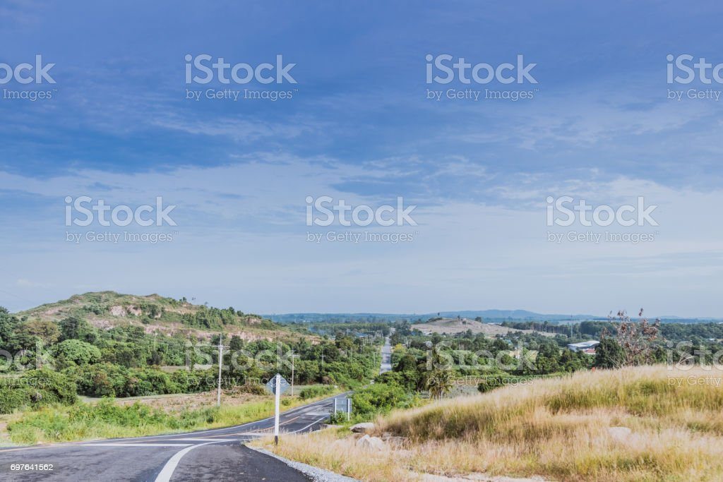 A serpentine road field and mountains stock photo