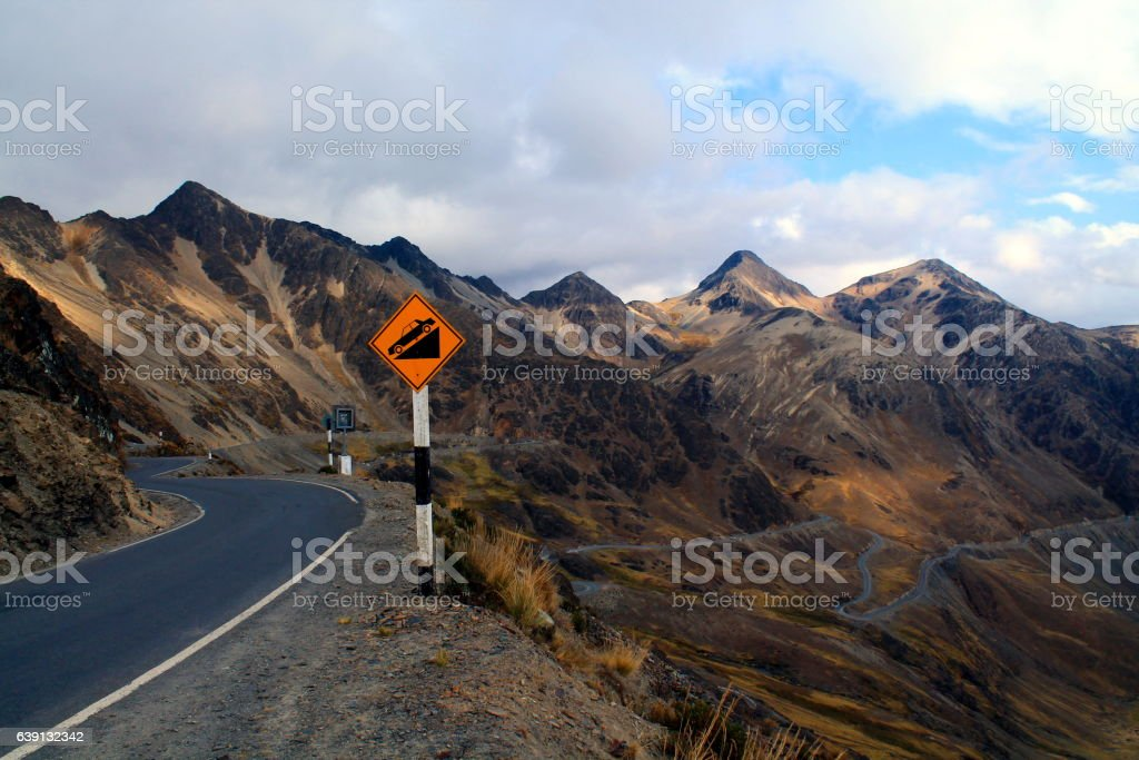 serpentine road in the foggy mountains with street sign stock photo
