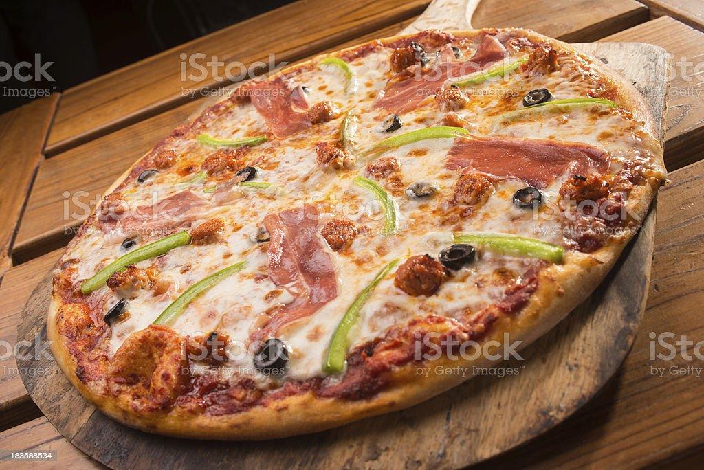 Serrano Ham Pizza on a Wooden Peel royalty-free stock photo