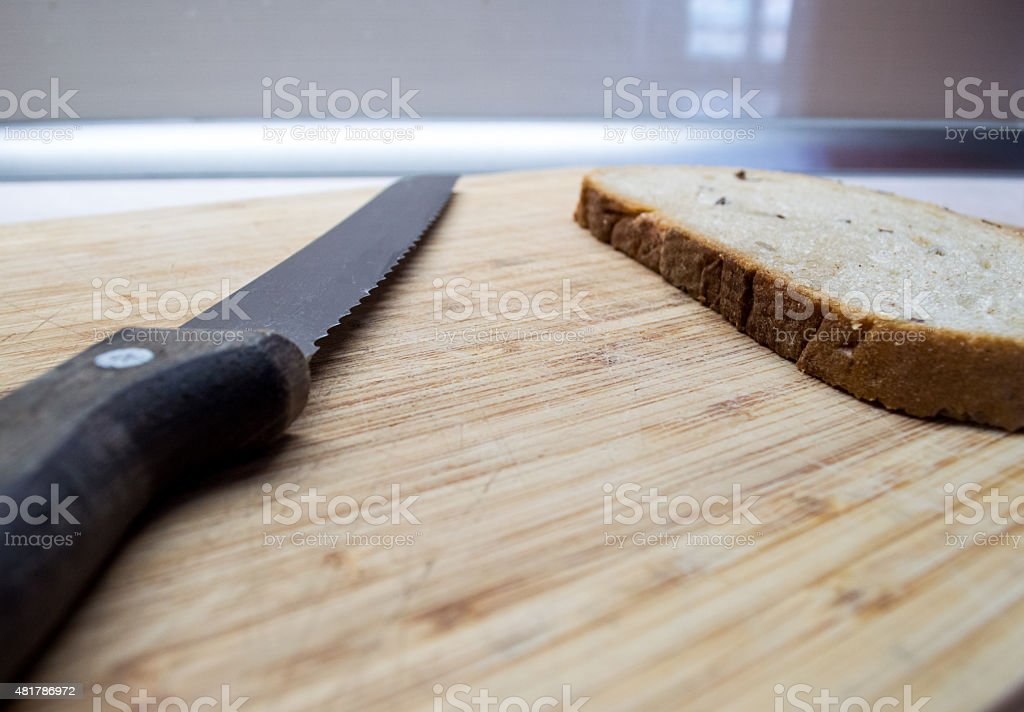 Serrated Bread Knife Blade with Bread Slice on Bread Board royalty-free stock photo