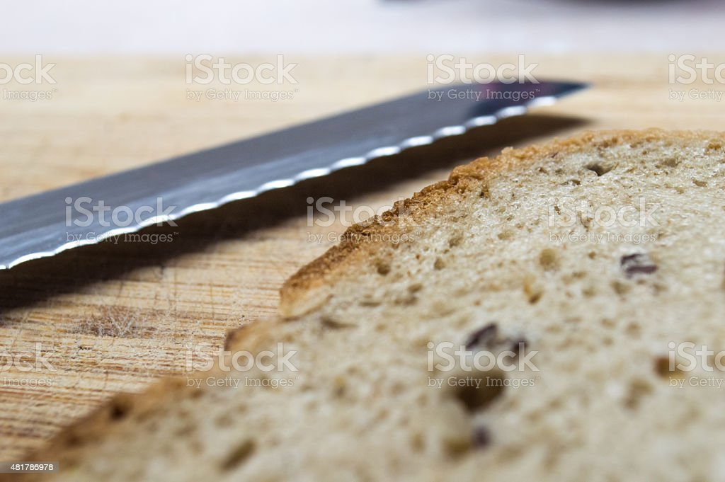 Serrated Bread Knife Blade with Bread Slice royalty-free stock photo