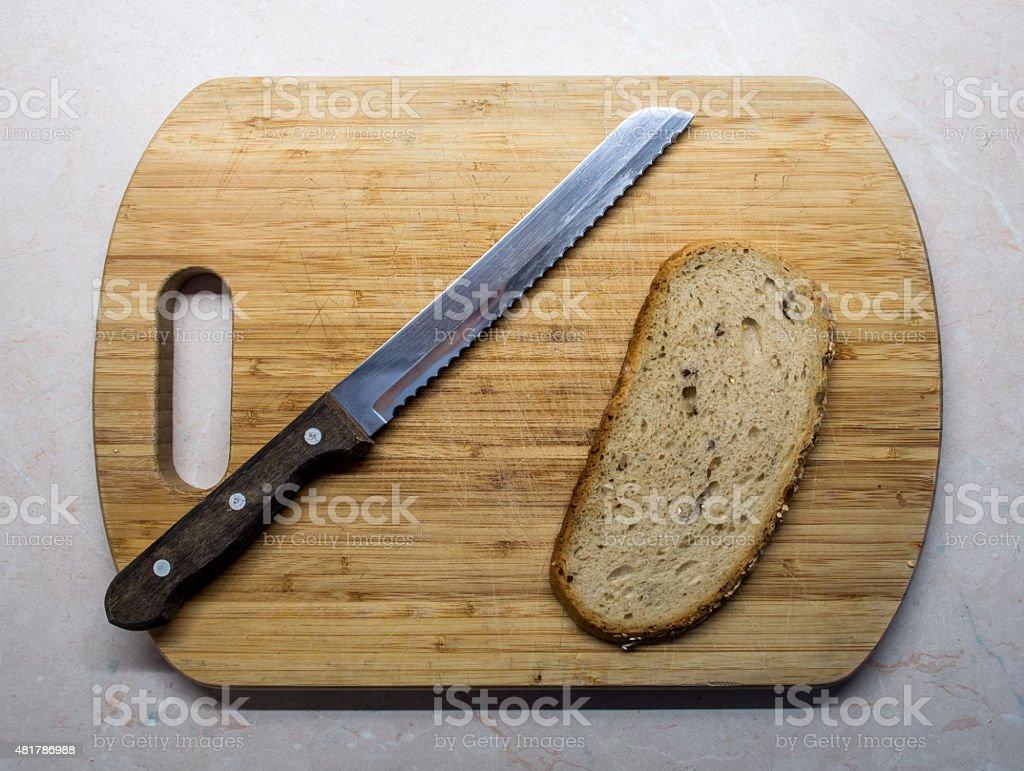 Serrated Bread Knife on Bread Board with Bread Slice stock photo