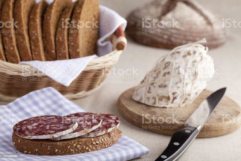 Served kitchen table, sandwich on napkin, salami, bread royalty-free stock photo