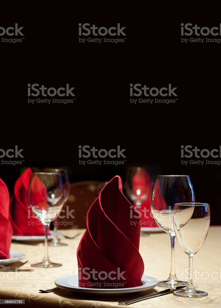 Served table in restaurant with red napkins, glasses, black background stock photo