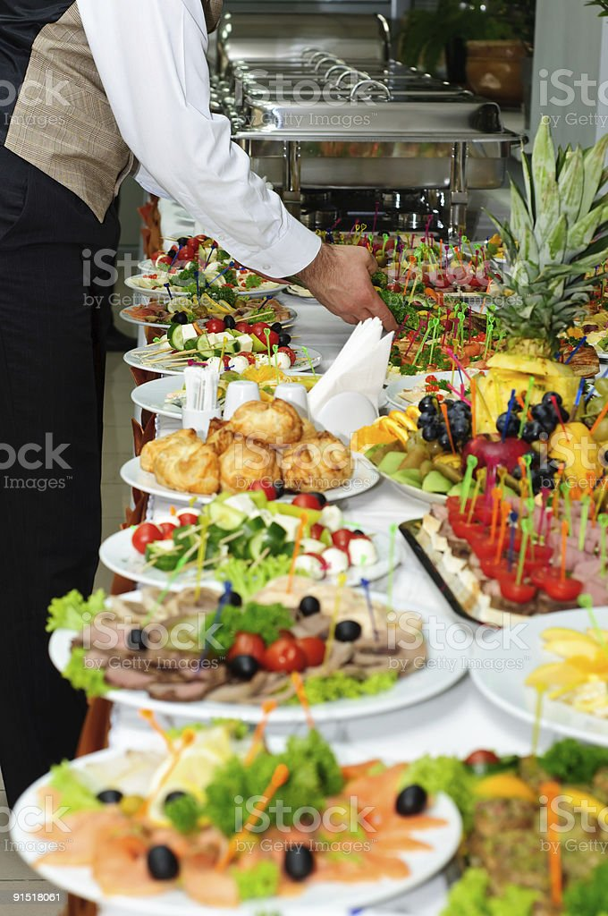 Server arranging food ready for banquet buffet stock photo