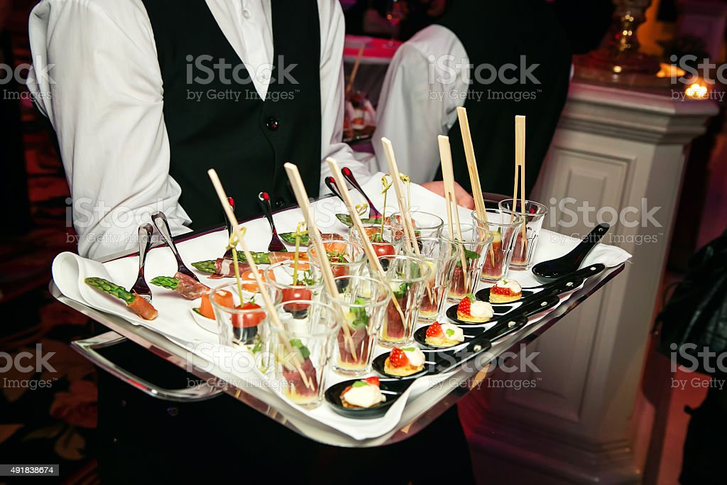 Server holding a tray of appetizers at banquet. stock photo