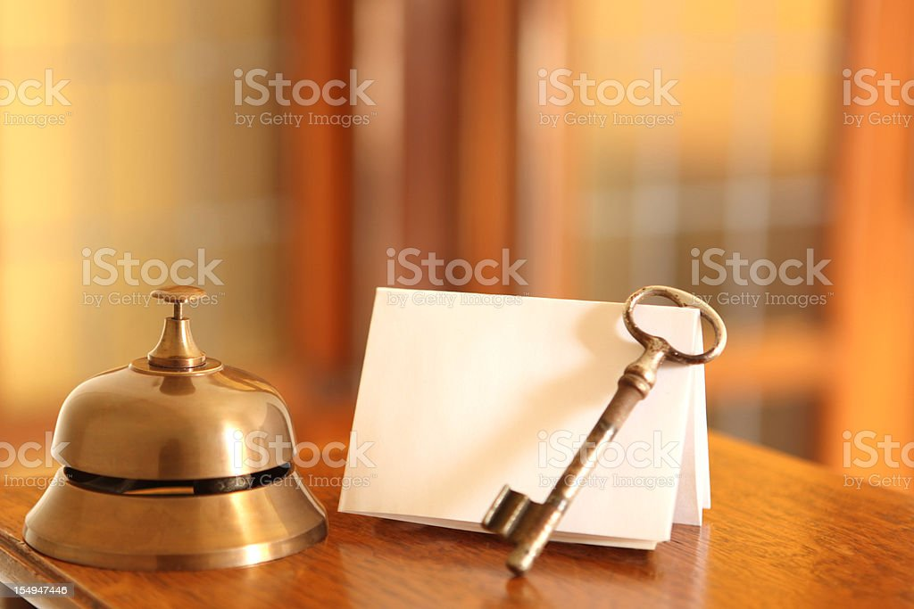 Service bell, old fashioned door key and card in hotel lobby stock photo