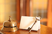 Service bell, old fashioned door key and card in hotel lobby
