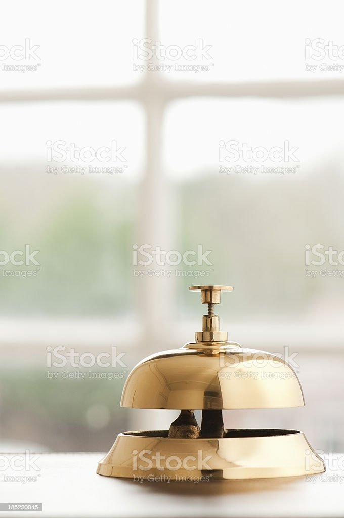 Service bell on desk beside window with copy space royalty-free stock photo