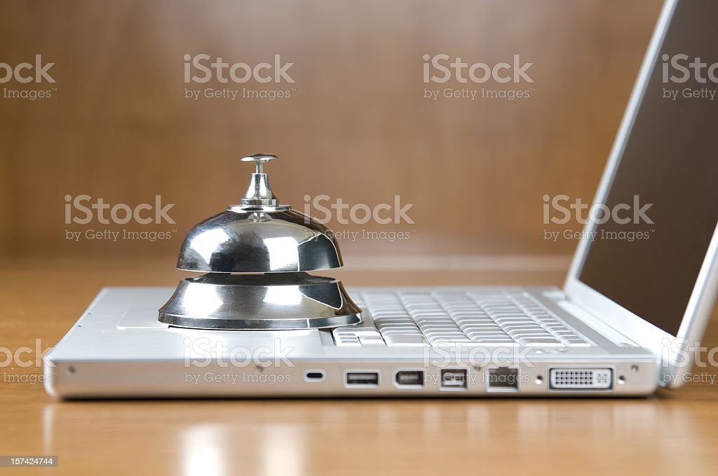 Service bell on white laptop. Online reservation royalty-free stock photo