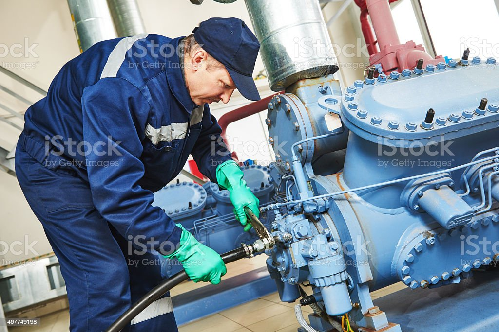 Service employee working on an industrial compressor station stock photo