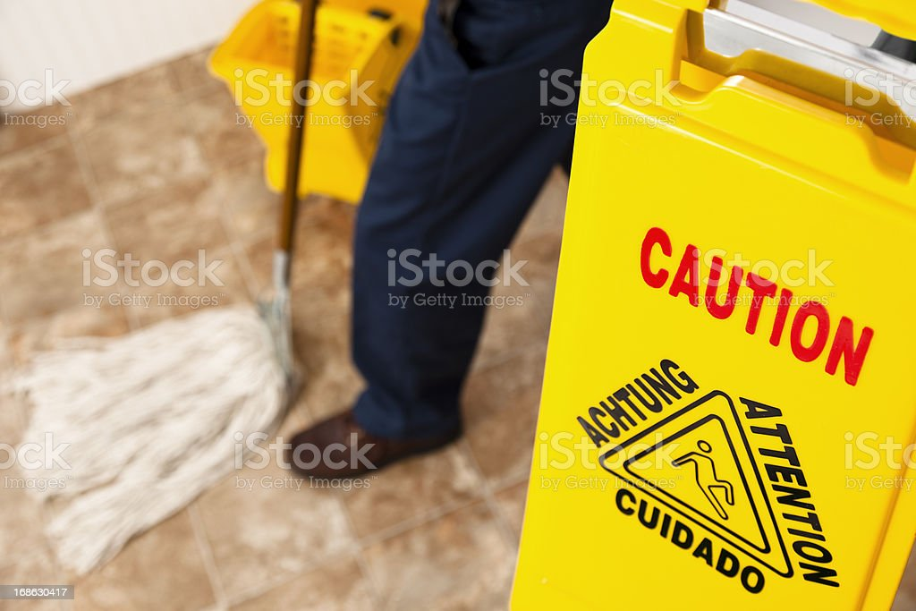 Service Industry:  Caution sign and janitor mopping retail store floor stock photo