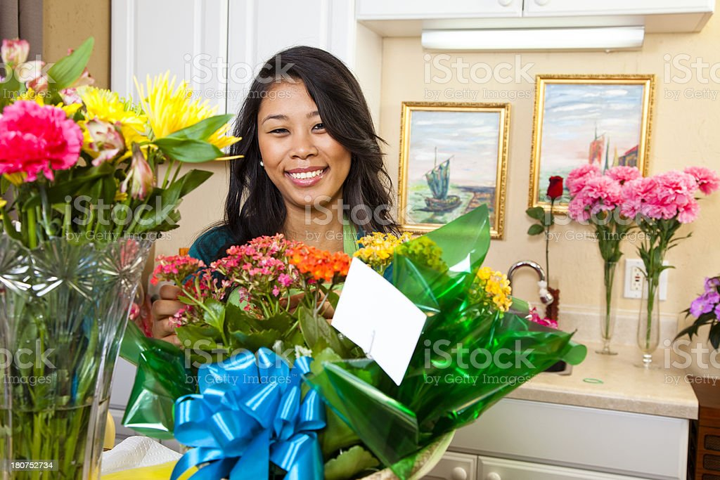 Service Industry: Employee presenting flowers at front desk. Floral arrangement stock photo