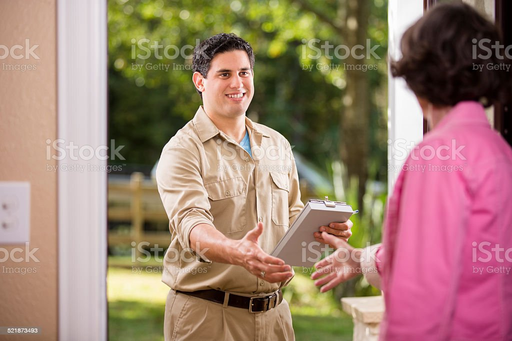 Service Industry: Latin descent repairman at customer's front door. stock photo