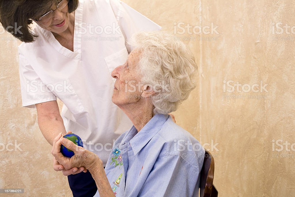 Service Industry: Physical Therapy for seniors. Nurse gives strength assistance royalty-free stock photo