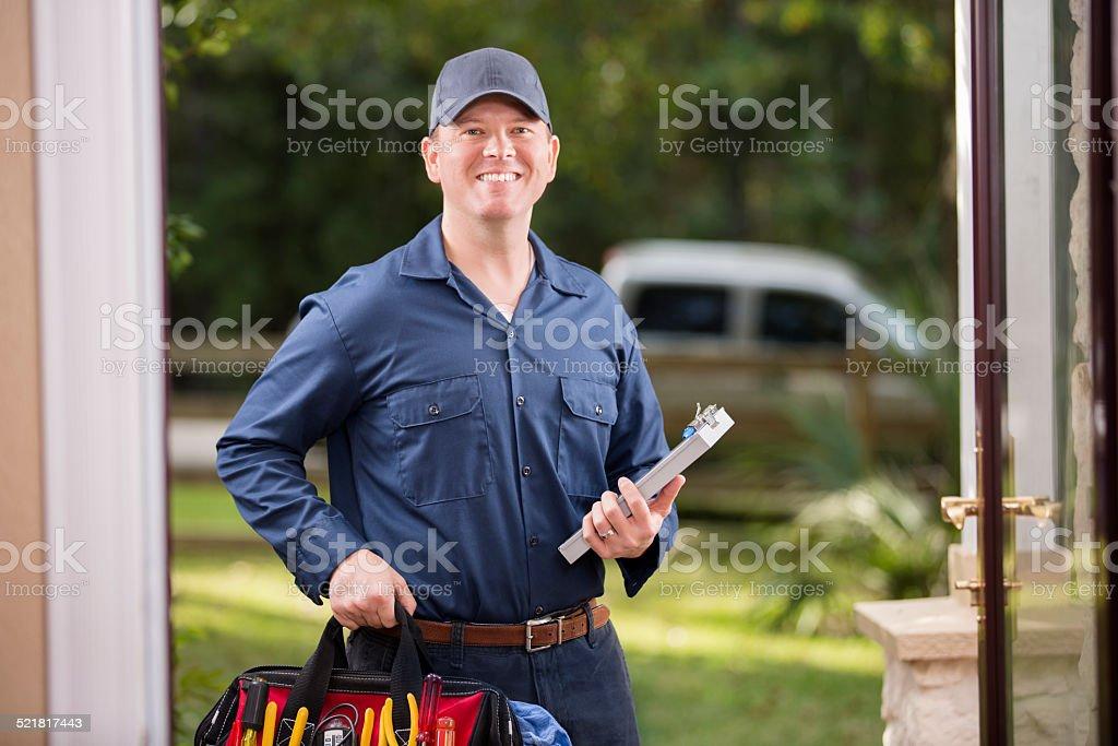 Service Industry: Repairman at customer's front door. stock photo