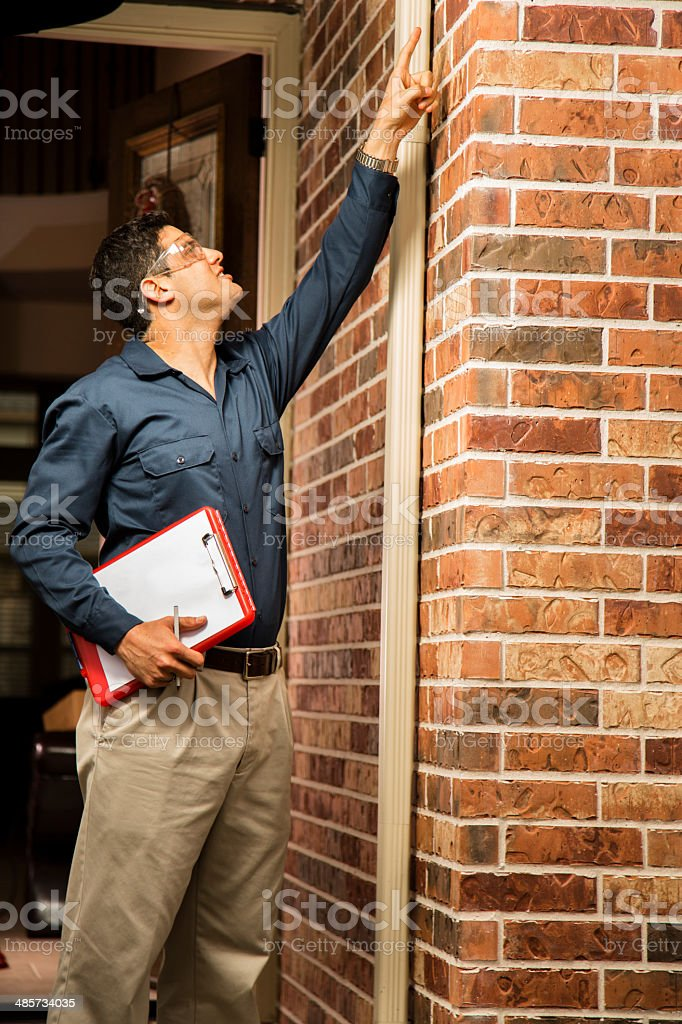 Service Industry: Repairman or inspector outside a home. stock photo
