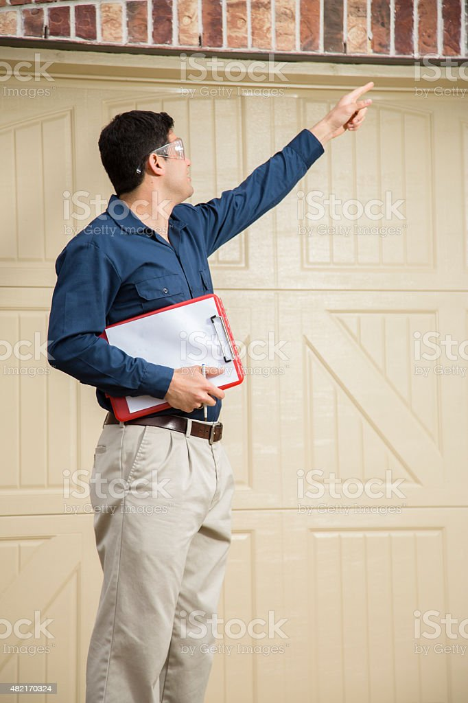 Service Industry: Repairman or inspector outside a residential home. Clipboard. stock photo