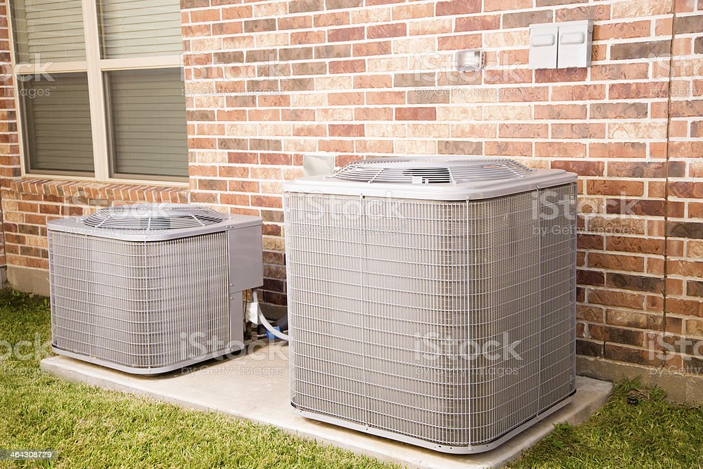 Service Industry: Two air conditioner units outside home. stock photo