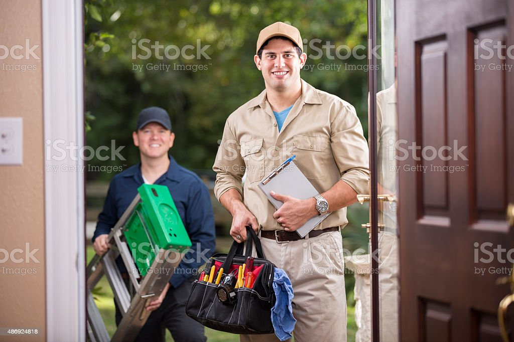 Service Industry: Two multi-ethnic repairmen at customer's front door. stock photo