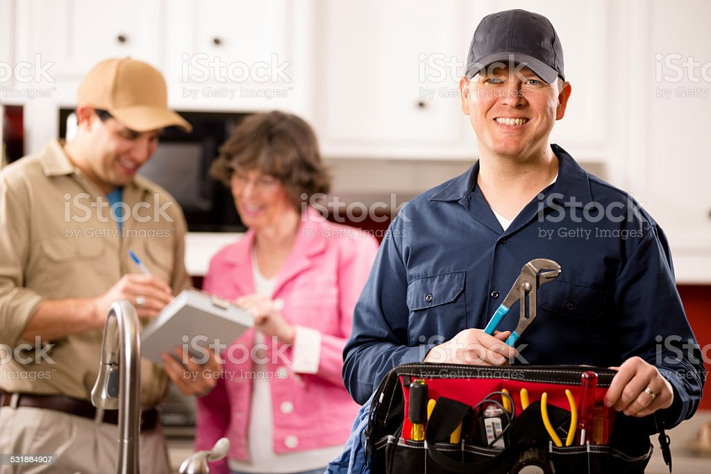 Service Industry: Two multi-ethnic repairmen work at customer's home. stock photo