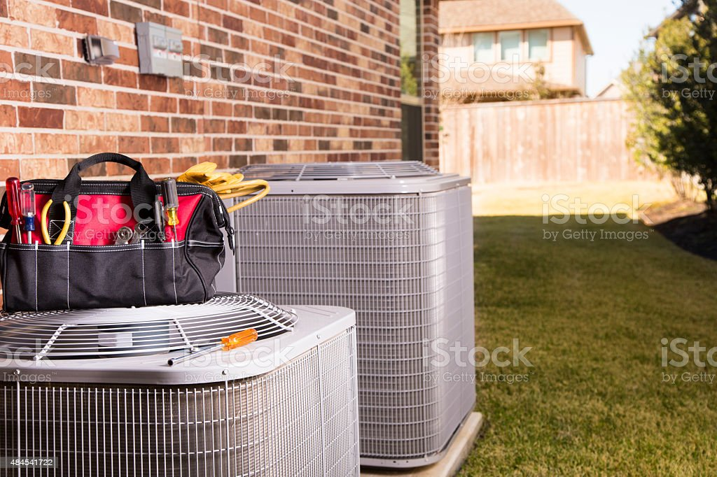 Service Industry:  Work tools, air conditioners. Outside residential home. Summer stock photo