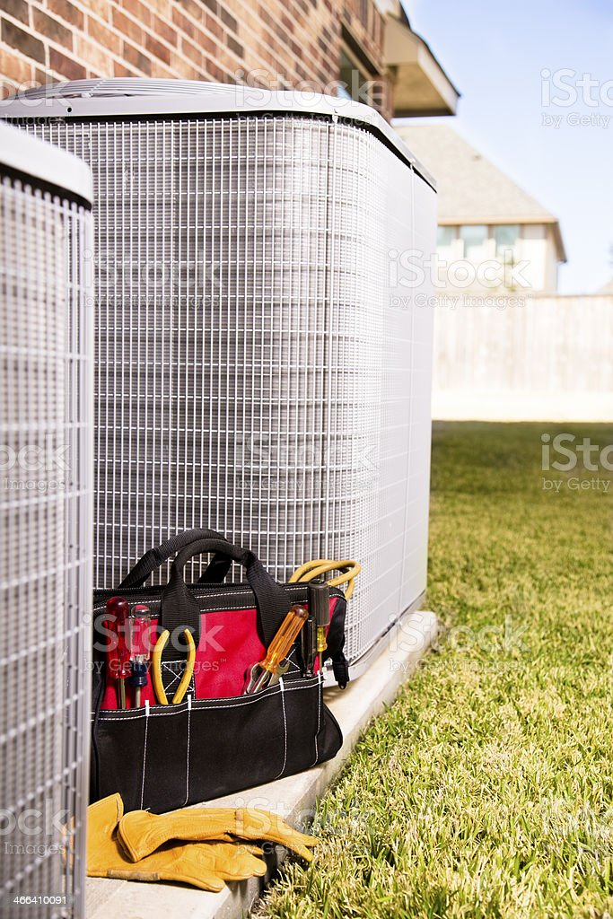 Service Industry:  Work tools, gloves beside air conditioners. Outside home. stock photo