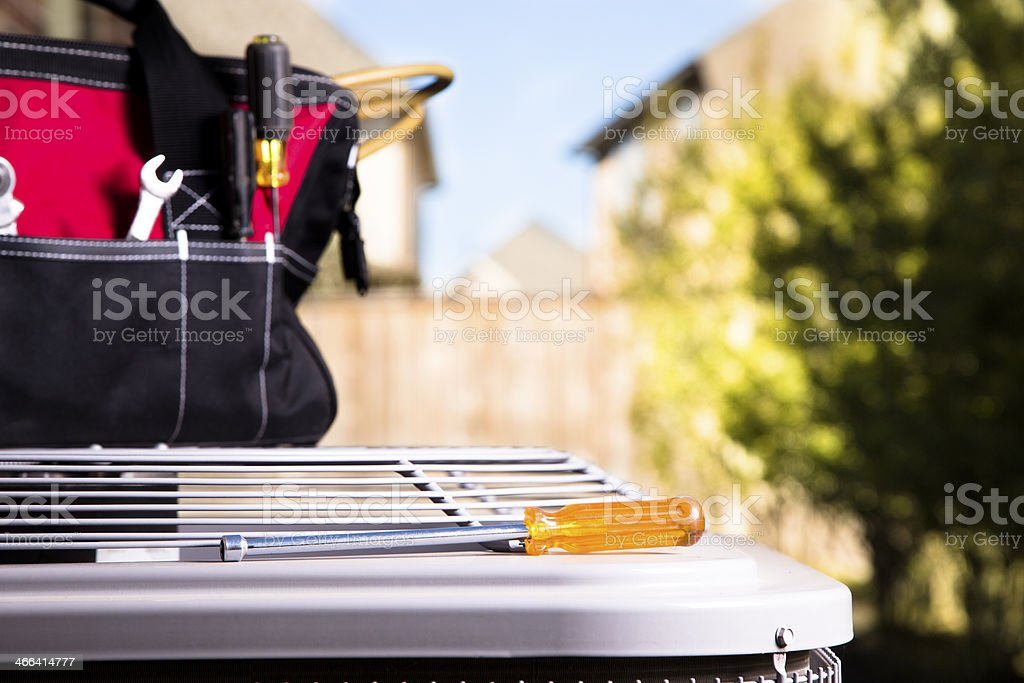 Service Industry:  Work tools on air conditioner. Outside home. stock photo