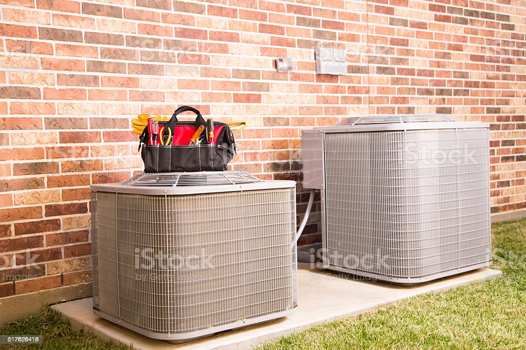 Service Industry:  Work tools on air conditioners. Outside home. stock photo