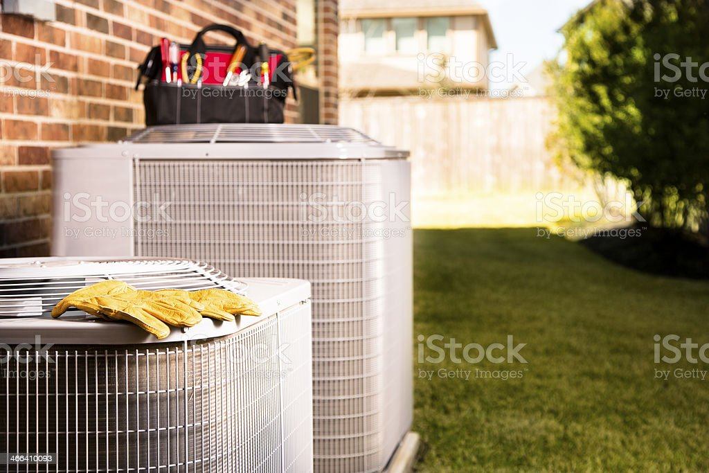 Service Industry:  Work tools on air conditioners. Outside residential home. stock photo