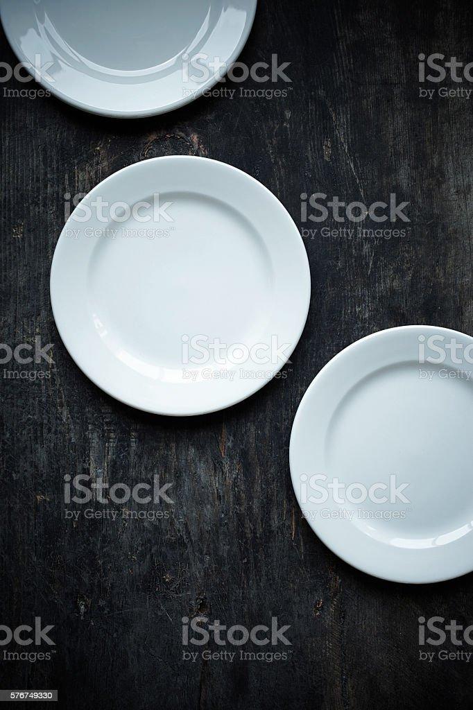 Service plates on dark wooden background stock photo