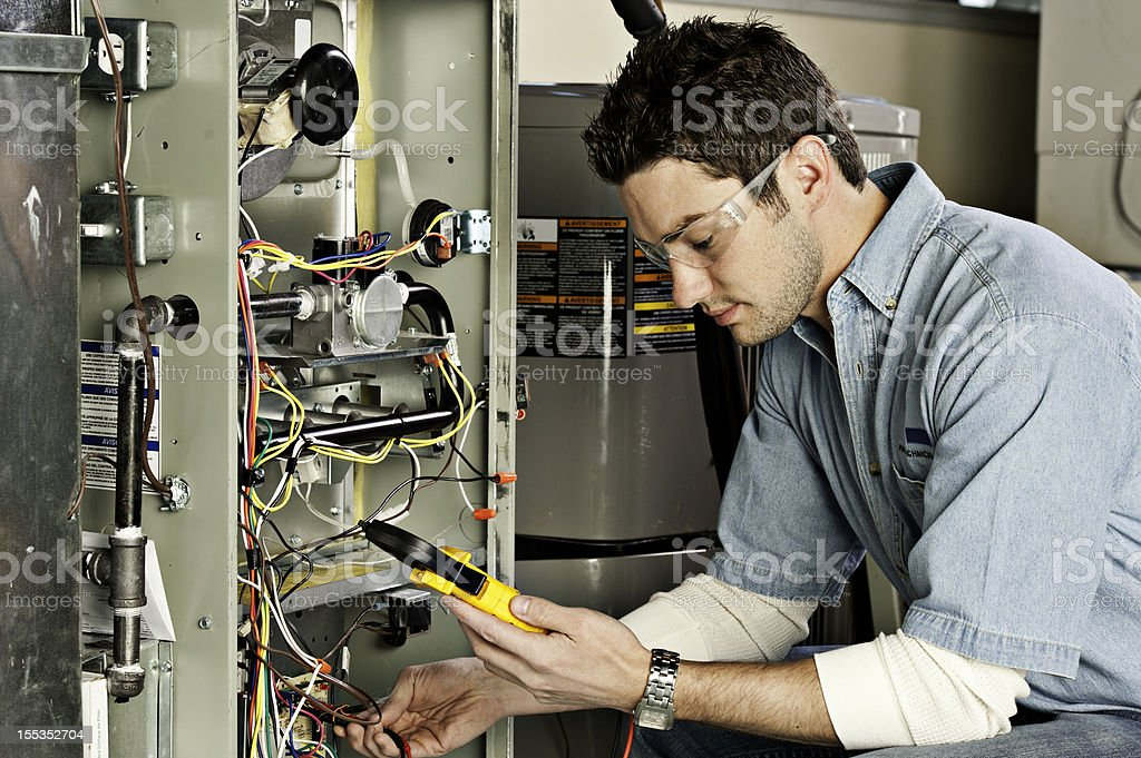 Service technician testing a furnace. stock photo