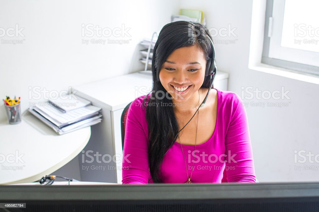 Service with a smile. Asian Office Lady at call centre stock photo