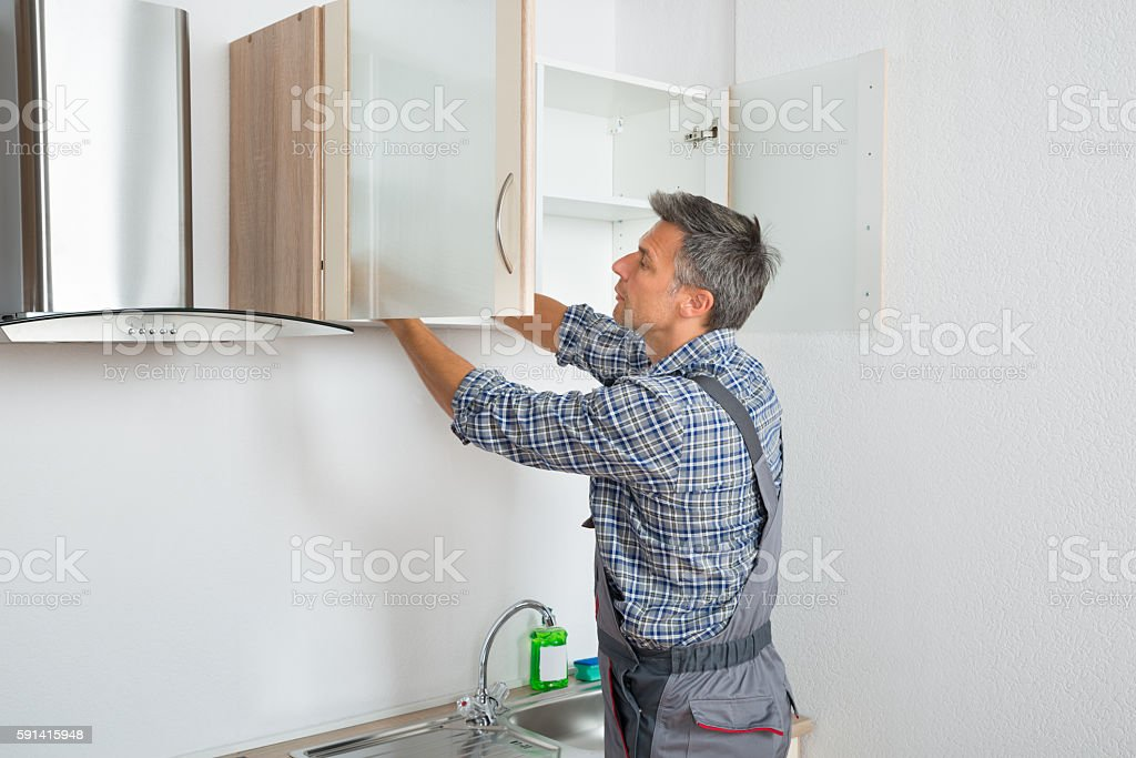 Serviceman Fixing Cabinet With Screwdriver In Kitchen stock photo
