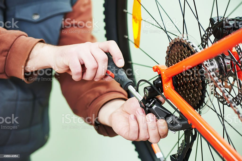 serviceman installing assembling or adjusting bicycle gear on wh stock photo