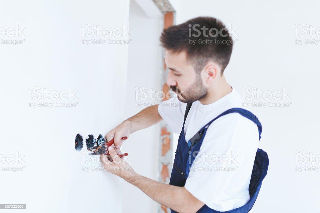 Serviceman is repairing home interior stock photo