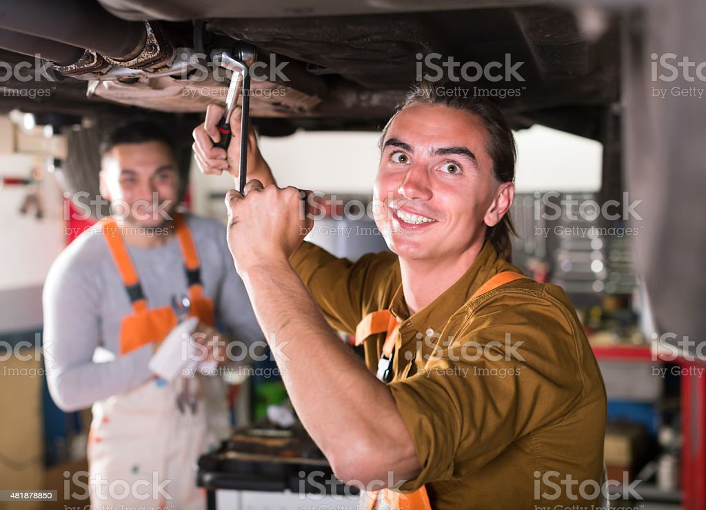 Serviceman repairing exhaust system stock photo