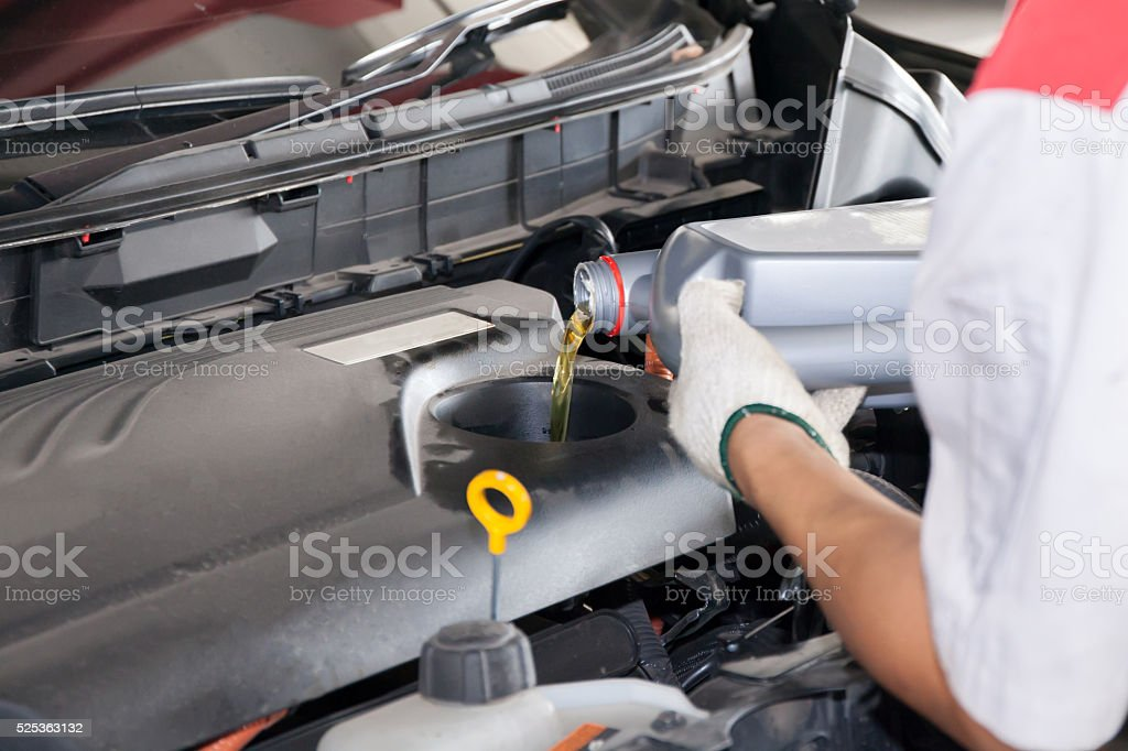 Servicing mechanic pouring new oil lubricant into the car engine stock photo