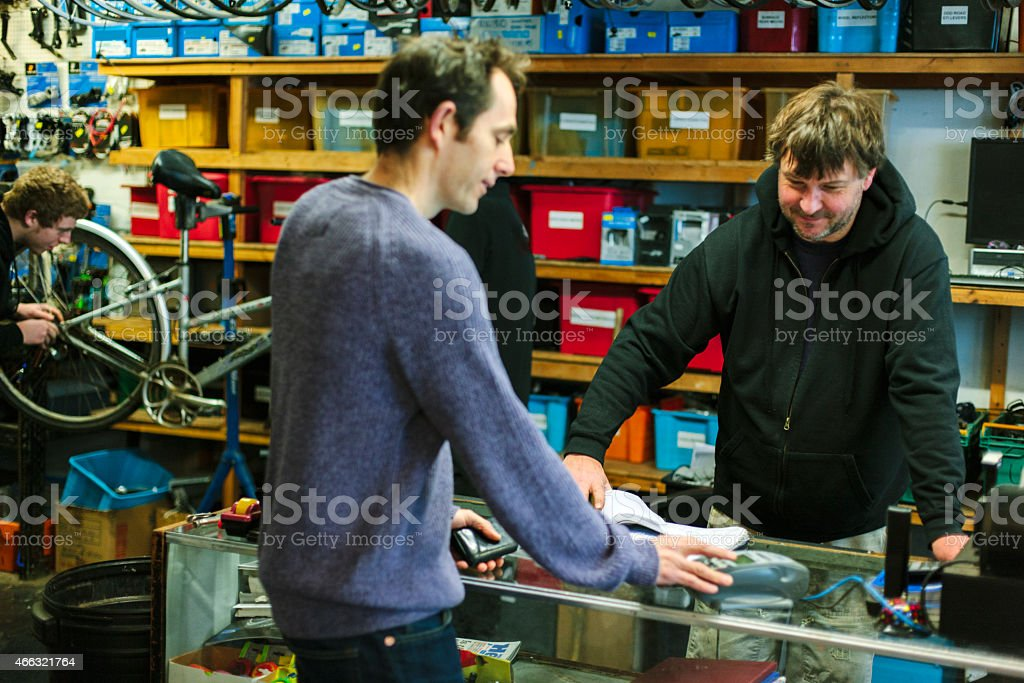 Serving a customer, bicycle shop, credit card payment stock photo