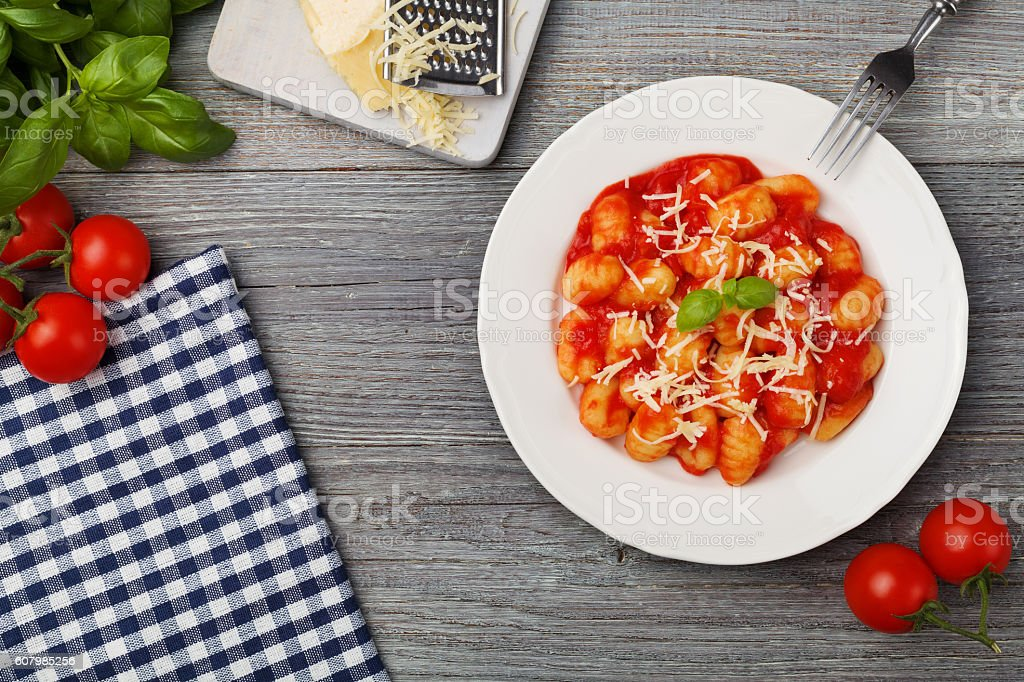 Serving gnocchi in tomato sauce with cheese. stock photo