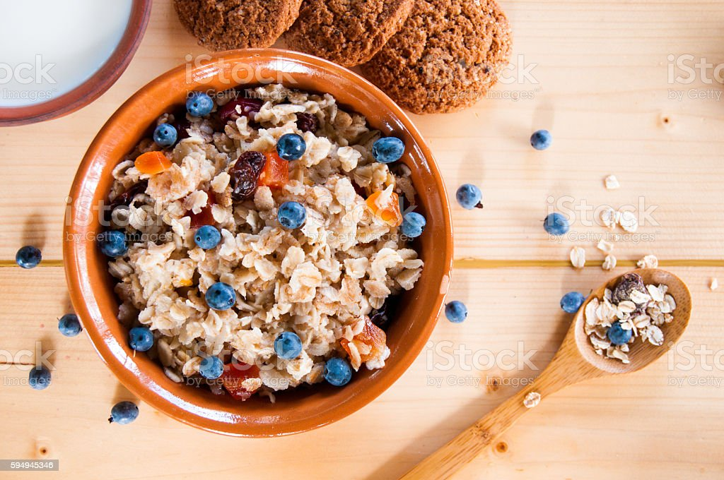 Serving muesli scattering of wild berries, cookies, milk on table stock photo