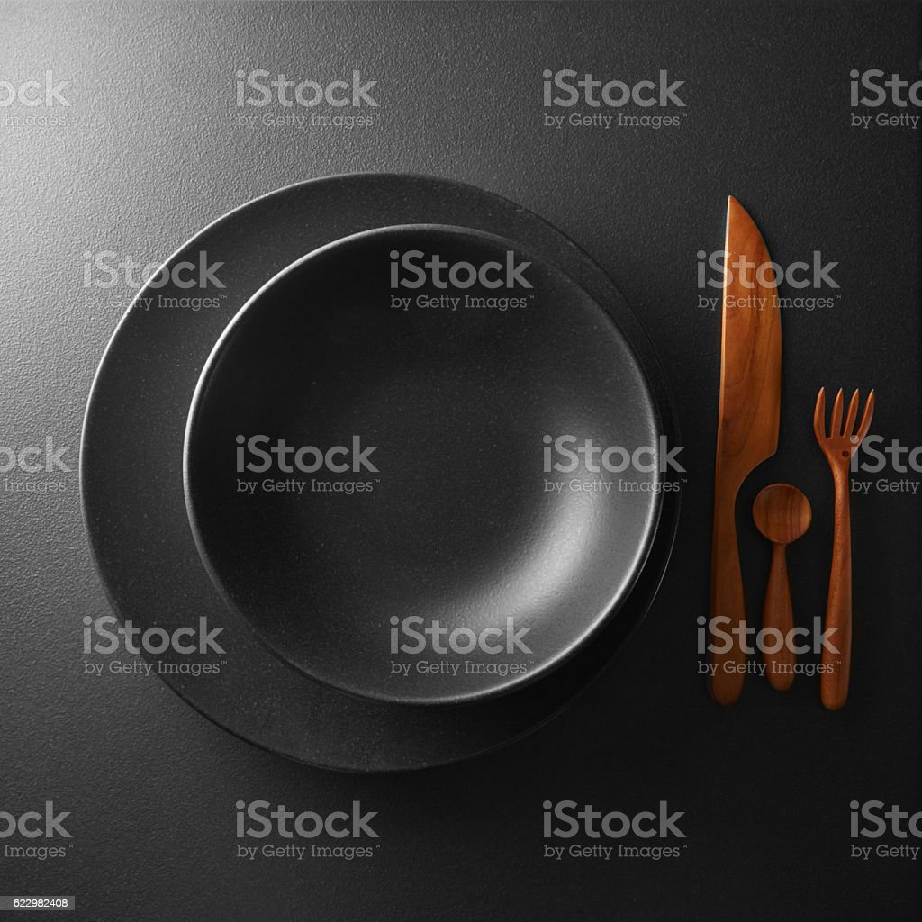 serving of black table with dark wooden utensils and cutlery stock photo