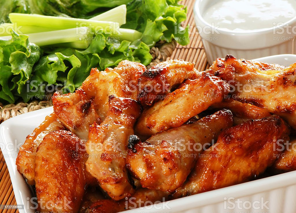 Serving of crispy chicken wings and salad stock photo