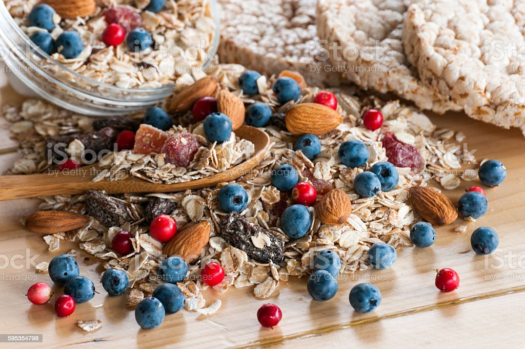 Serving of wild berries cereal, crispbread bulk on wooden table stock photo