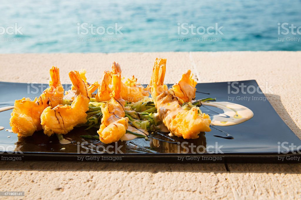 Serving plate with crispy shrimps and salad royalty-free stock photo
