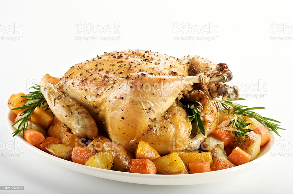 Serving platter with a roasted chicken and baked vegetables royalty-free stock photo