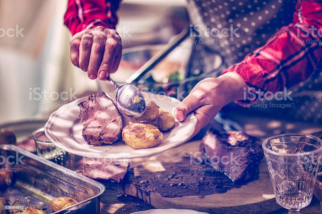 Serving Roast Beef with Potatoes and Root Vegetables stock photo